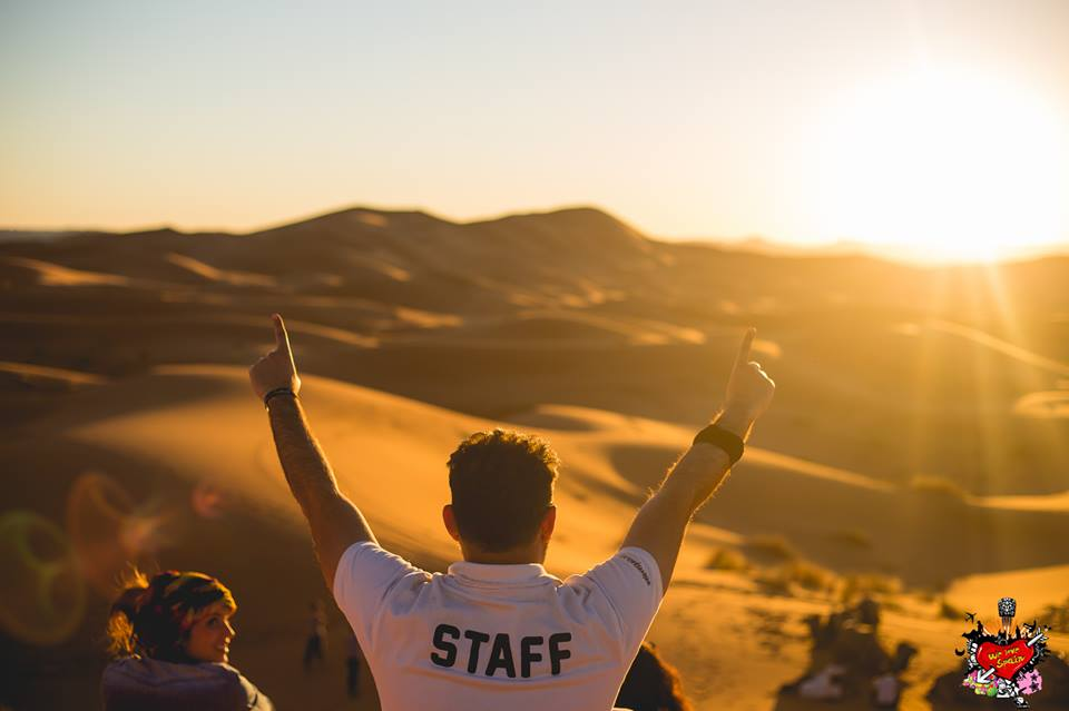 We Love Spain Coordinator watching sunset with hands in the air in Sahara Desert, Merzouga Morocco
