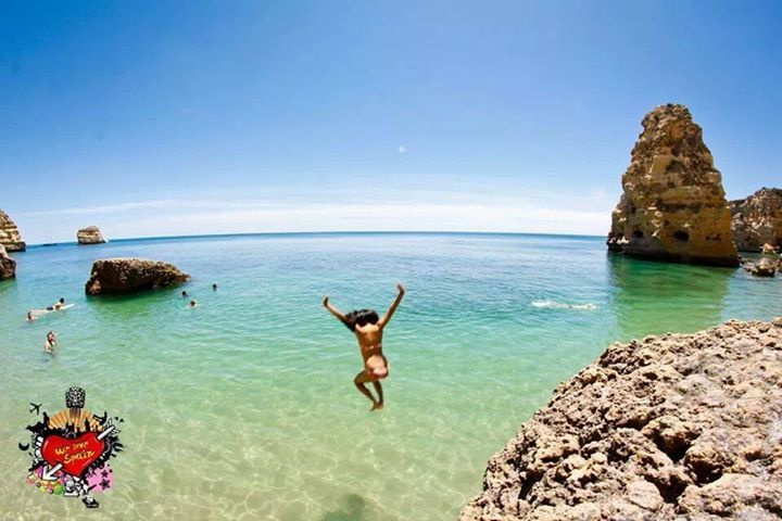 international student jumping off rock at marinha beach portugal on the we love spain beach day trip